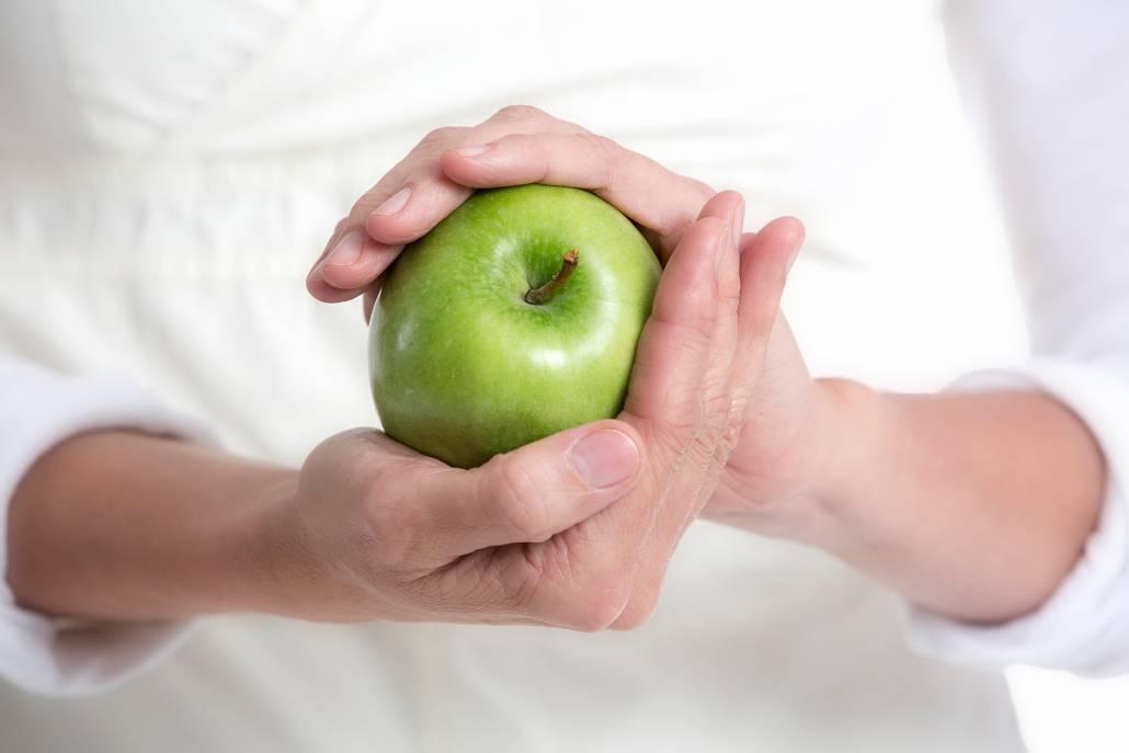 Hände umfassen grünen Apfel – Heilpraktikerin Sabine Schmidt TCM in Bremerhaven